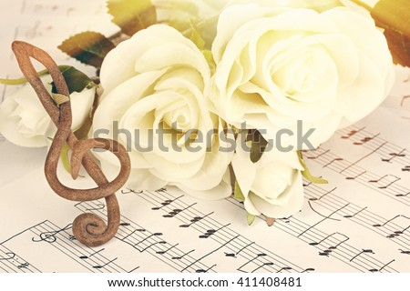 Treble clef and roses on music notes background. Retro style - stock photo