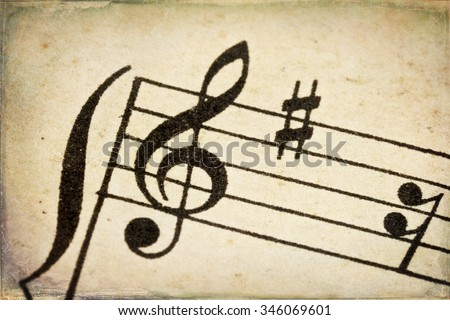 treble clef - macro of sheet music on vintage paper with added grunge texture and border - stock photo