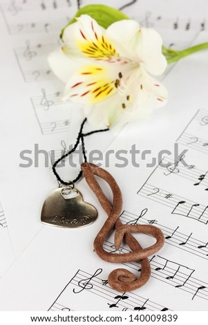 Treble clef, pendant and flower on musical background - stock photo