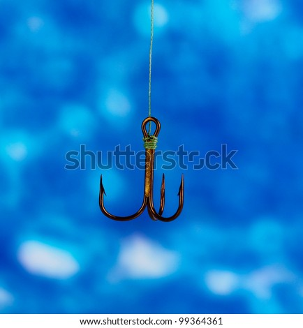 Treble fish hook on blue background - stock photo