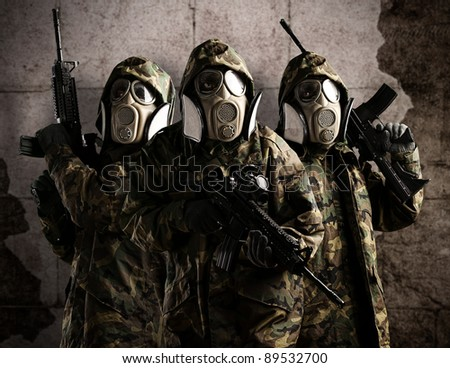 Tree armed soldiers with gas mask and rifles against a grunge bricks wall