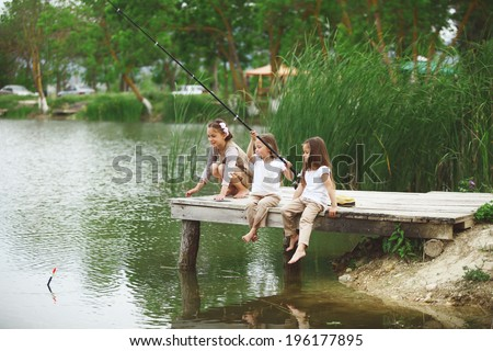 Tree children fishing in pond in summer - stock photo