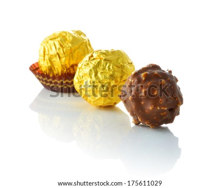 Tree chocolate balls with almond in a gold foil paper on white background. front view