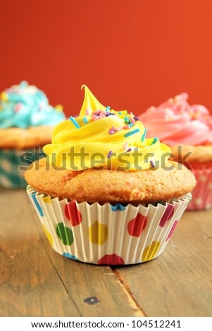 Tree colorful cupcakes with candies on an orange background