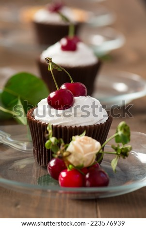 Tree cupcakes with whipped cream and cherries on wooden table, shallow DOF. - stock photo