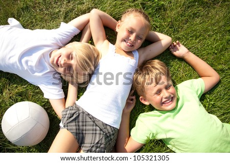 Tree cute children  lying in green grass and enjoying summertime