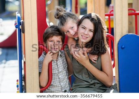 Tree different aged kids posing on playground. - stock photo