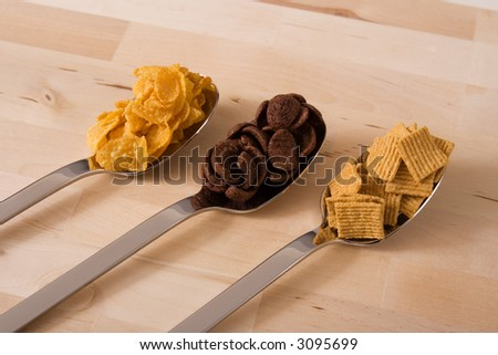 Tree different kind of cereals in tree spoons over a wood background - stock photo
