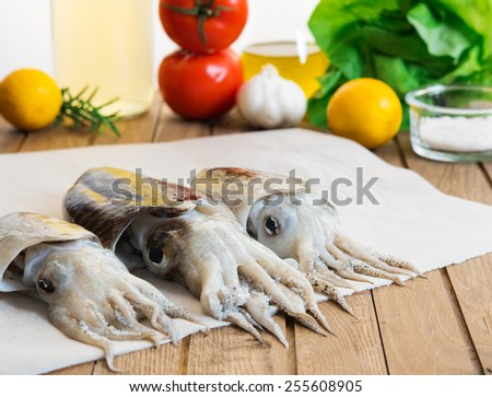 Tree fresh cuttlefish, on background vegetables, olive oil and wine. Light wooden table. Focus on tentacles - stock photo
