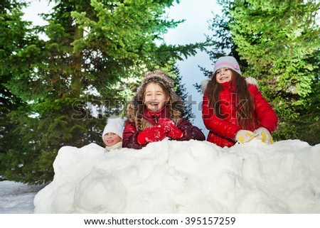 Tree girls playing snowballs at sunny winter day - stock photo