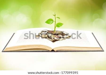 "tree growing from book with coins / A big open book with coins and tree. ""Reading makes you richer"" concept."