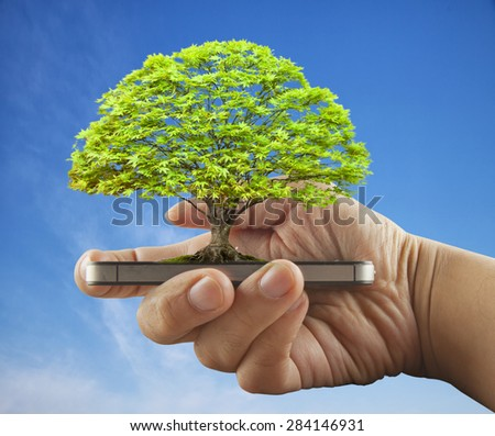 Tree growing over smartphone in male hand, blue sky, horizontal image