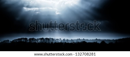 Tree lined landscape with sunrays through clouds - stock photo