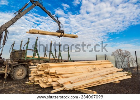 Tree log hydraulic manipulator - tractor on sunny day - stock photo