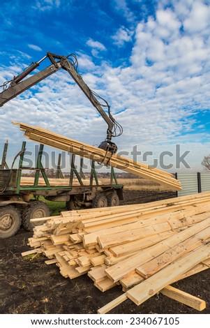 Tree log hydraulic manipulator - tractor on sunny day - stock photo