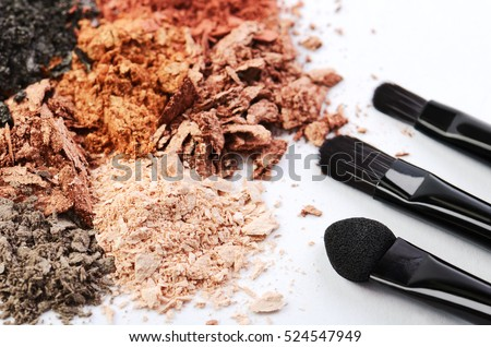 tree makeup brushes and crumbled eyeshadow of different colors on a white background