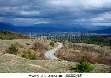 Tree near the highway in the field against stormy sky - stock photo