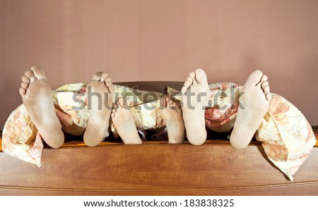 Tree pairs of legs of the happy family in bed - father, mother and child - stock photo