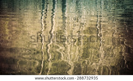 Tree reflections in an Alaskan lake forming abstract patterns processed for an artistic look. - stock photo