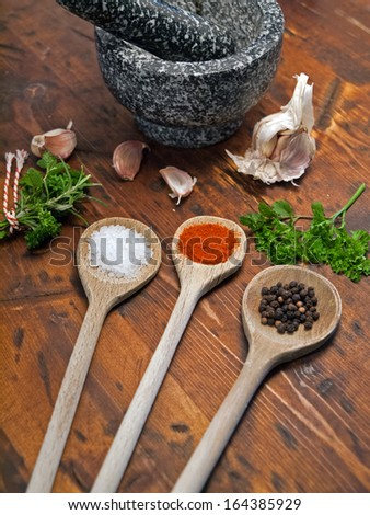 Tree spoons with spices, garlic and a bundle of herbs, mortar and pestle