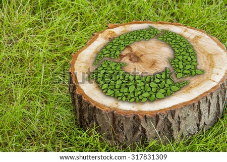 tree stump on the green grass with recycle symbol - stock photo