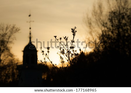 Trees & a church silhouetted by the setting sun.  Mission Church, Mackinac Island, MI, USA. - stock photo