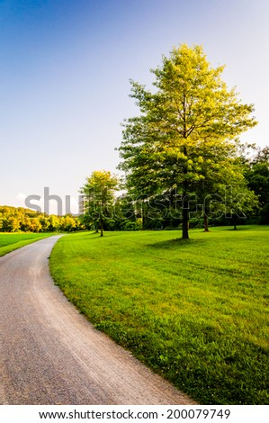 Trees and lawn along dirt path in Southern York County, Pennsylvania. - stock photo