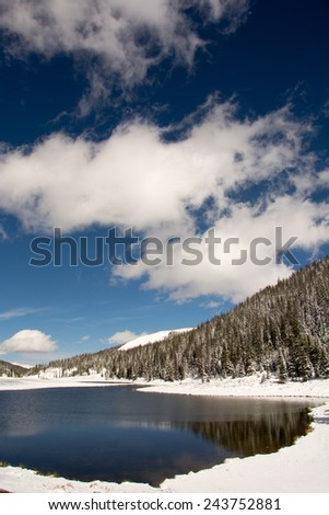 Trees blanketed with snow with a blue sky and a pond along Trail Ridge Road in Rocky Mountain National Park in Colorado - stock photo