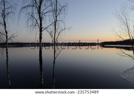 trees by lake at sunset in winter - stock photo