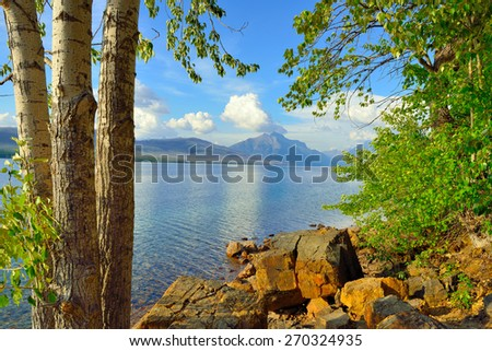 trees in front of the McDonald lake with Mountains in Glacier National Park, Montana in summer - stock photo