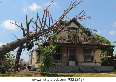 Trees in the direct impact of an EF-5 tornado are heavily damaged, causing further destruction to already fatally damaged man made structures. - stock photo