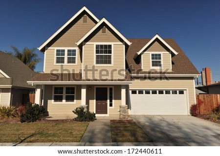 Trees next to a two story house with sloping driveway - stock photo