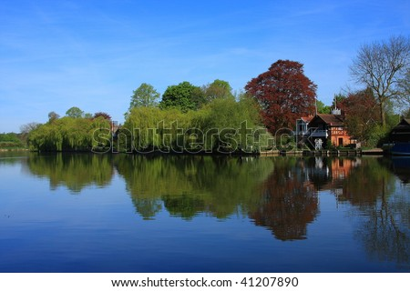 Trees reflect in a peaceful River Thames at Cookham in Berkshire, UK - stock photo
