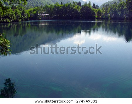 Trees reflected in blue water alpine lake