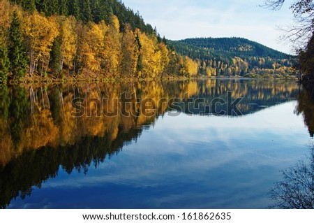 Trees with autumn leaves gold mirror above the surface of the pond, wooded mountains in the background - stock photo