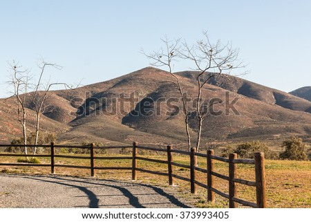 Trees with fence and Mountains at Lower Otay Lakes in Chula Vista, California.  - stock photo