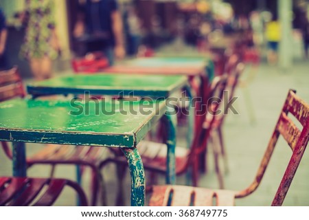 treet view of a Cafe terrace with tables and chairs in european city - stock photo