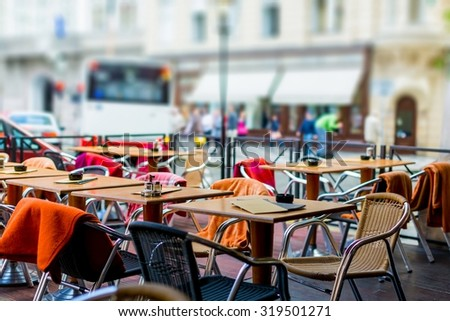 treet view of a Cafe terrace with tables and chairs in european city. Toned photo. soft focus - stock photo