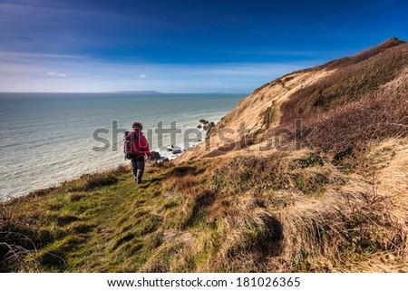 trekker walk on a path in lulworth england - stock photo