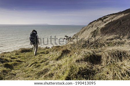 trekker walk on a path in lulworth england - stock photo