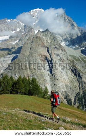 Trekker walking along a mountain path, in background the Mont Blanc valley, west Alps, Italy. - stock photo