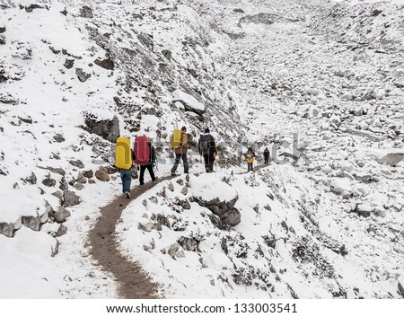 Trekkers going to Everest Base Camp in snowstorm - Nepal, Himalayas - stock photo
