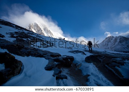 Trekkers going to see Mt. Everest up close attempt to climb to the top of Kala Patthar in Sagarmatha National park, Nepal. Mount Pumori view on the left. - stock photo