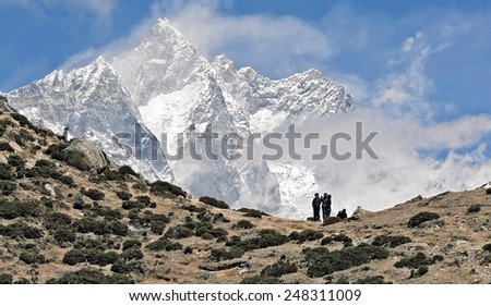 Trekkers in the Himalayas standing against peak Lhotse (8516 m) - Nepal - stock photo
