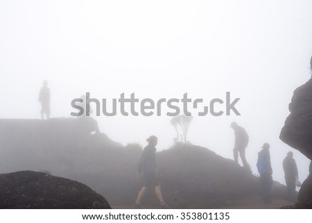 Trekkers walking in the midst of clouds, mist and fog on the top of Mount Roraima in Canaima national park in Venezuela.