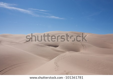 Trekking across the desert.  Two men walking off in the distance across the rolling dessert, leaving a winding trail of footprints in the rolling sand dunes