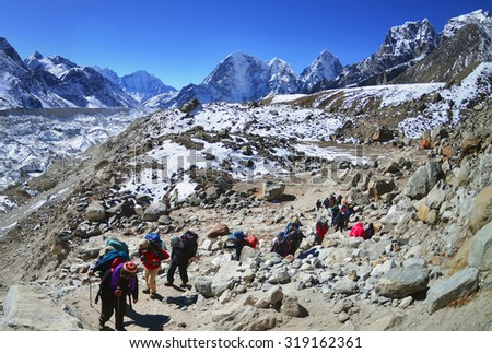 Trekking in Himalaya. Group of hikers  with backpacks   on the trek in Himalayas, trip  to the base camp Everest  - stock photo