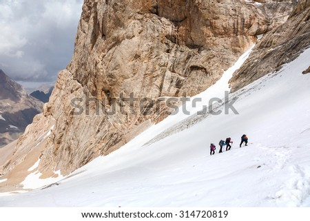 Trekking in Himalaya Hikers Walking Up on Glacier in Nepal India Himalaya Way up to high altitude famous attraction with Snow Climbing and trekking gear mountain sunny day Rock Moraine on background - stock photo