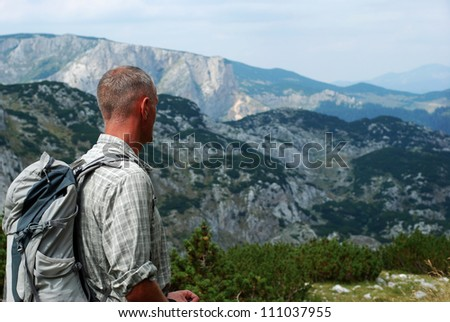 Trekking in Montenegro. Backpackers looking at the mountains - stock photo