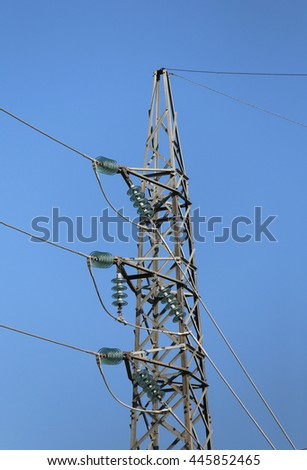 trellis with electric cables in aluminum of high voltage to transport the electrical energy and many glass insulators - stock photo